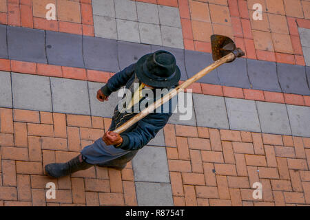 COTACACHI, ECUADOR, NOVEMBER 06, 2018: Above view of unidentified indigenous man walking in the sidewalk and holding in his back a farm machine, located in the city of Cotacachi - Stock Photo
