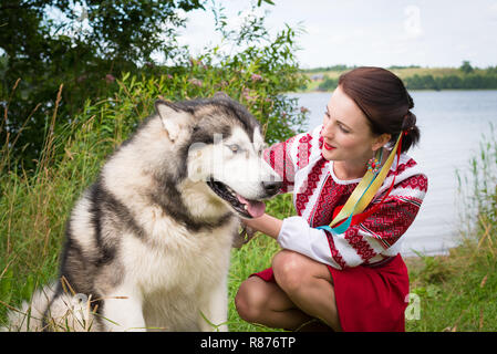 Girl dresses in a traditional Slavic attire petting a dog - Stock Photo