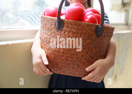 girl in navy blue striped dress handing basket of red hearts represents helping hands, family support, morale, purity, innocence, cheer up, loves, hos