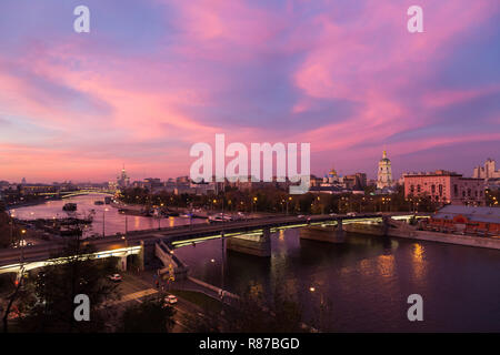 Evening, twilight and night view, red sunset over Moskva river and red skies, New monastery of the Saviour and Novospasskiy Bridge in Moscow, Russia. - Stock Photo