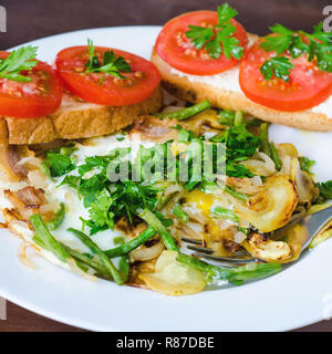 scrambled egg with tomato, parsley and bread - Stock Photo