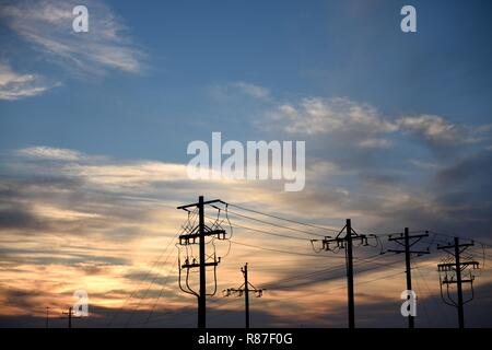 High voltage substation and utility pylons, silhouette at sunset in Wyoming / USA. - Stock Photo