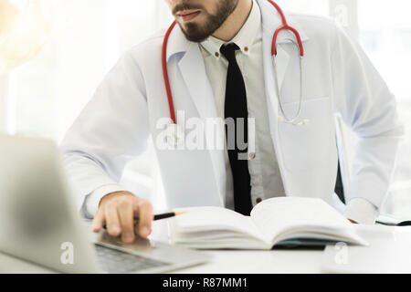 Doctor using laptop and electronic medical record (EMR) system. Digital database of patient's health care and personal information on computer screen. - Stock Photo