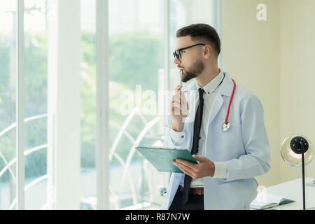 Portrait of Young Caucasian male Doctor is posing with arms crossed and looking through the window. copy space. Thinking. - Stock Photo