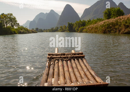 Front of bamboo raft in foreground on Yulong River, Yangshuo, China. Limestone cliffs in silhouette along edge of river. - Stock Photo