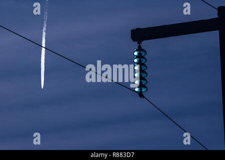 115 Kv High tension power lines supported high above the ground using wooden poles on a clear sunny day with a commercial jet passing above. - Stock Photo
