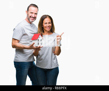 Middle age hispanic casual couple buying new house over isolated background very happy pointing with hand and finger to the side - Stock Photo