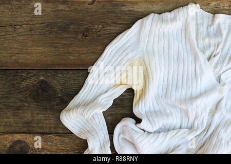 Yellow stain on  jacket on the old wooden background. Top view. Flat lay. - Stock Photo