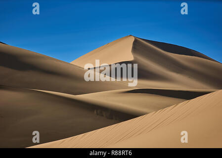 Sand dunes in the desert , warm dry sand under blue sky - Stock Photo