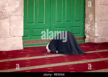 Young praying woman falling on knees against mosque Dome of the Rock in the Muslim quarter of the old city of Jerusalem in Israel - Stock Photo