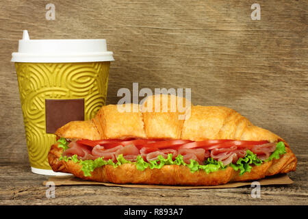 Big croissant with green salad, tomatoes and pork meat and paper coffee cup on old wooden background - Stock Photo