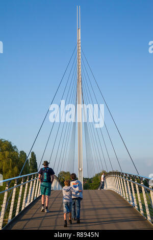 Two children and their father cross the Christchurch bridge in Reading, Berkshire - Stock Photo