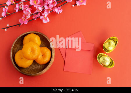 Flat lay Chinese New Year Background - Cherry Blossom, Mandarin Orange, Red Envelop and Golden Ingots on red background.