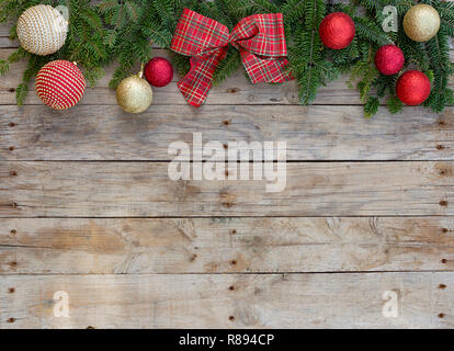 Christmas postcard frame on wooden background. For greeting card. Red and golden glitter balls, fir tree branches and checked red tie. Xmas. Christmas - Stock Photo