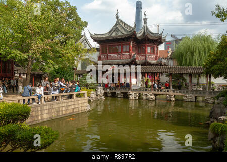 Tourists walking around shops in the Yu Yuan (Yuyuan) bazaar, Shanghai, China. Overcast sky, pond in foreground. - Stock Photo