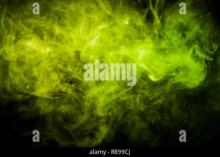 Dense multicolored smoke of   green and yellow colors on a black isolated background. Background of smoke vape - Stock Photo