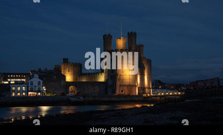 Caernarfon Castle, often anglicized as Carnarvon Castle, is a medieval fortress in Caernarfon, Gwynedd, north-west Wales. Taken here lit up at night - Stock Photo