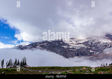 snowy mountain top through white clouds in summer - Stock Photo