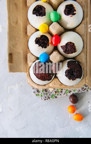 Dark chocolate brownie dessert in egg shells. Easter or funny kids party concept. White stone background. - Stock Photo