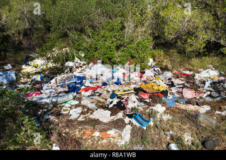 view of a pile of garbage illegally dumped in an open dump by a rural lane - Stock Photo