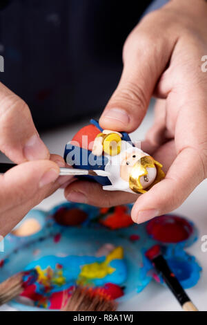 closeup of a caucasian man painting a handmade maggi figurine for a nativity scene - Stock Photo