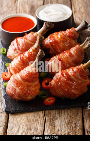 Spicy Lollipops fried chicken legs wrapped in bacon served with sauces close-up on a slate board on the table. vertical - Stock Photo