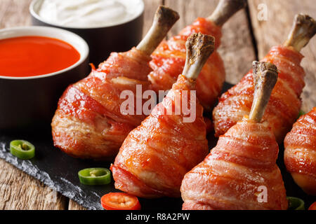 Delicious Lollipops chicken legs wrapped in bacon with sauces close-up on a slate board on the table. horizontal - Stock Photo