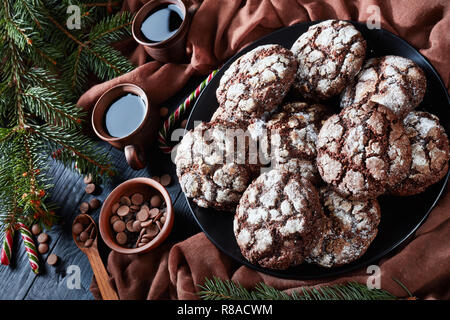 Christmas Chocolate Crinkle cookies on a plate on a black wooden table with fir tree, candy canes, brown cloth and cups of coffee, rustic style, horiz - Stock Photo