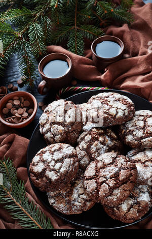 close-up of Christmas Chocolate Crinkle cookies on a plate on a black wooden table with fir tree, candy canes, brown cloth and cups of coffee, rustic  - Stock Photo