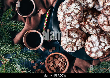 close-up of Christmas Chocolate Crinkle cookies on a plate on a black wooden table with fir tree, candy canes, brown cloth and earthenware cups of cof - Stock Photo