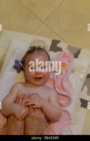 Smiling infant laying on the ground in the bathroom on blankets being massaged by two hands after the bath - Stock Photo