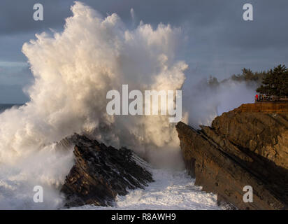 Charleston, OREGON, USA. 14th Dec, 2018. Storm watchers at a viewing area, right, are dwarfed as a massive wave crashes against rocks at Shore Acres State Park near Charleston on the south coast of Oregon. The National Weather Service issues a high surf warning for Oregon with powerful west swell predicted to create breakers of 28 to 32 feet through Monday afternoon. Credit: Robin Loznak/ZUMA Wire/Alamy Live News - Stock Photo