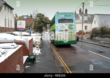 English village thawing after snow with double decker bus in motion passing snow covered houses, Totland Bay, Isle of Wight, UK - Stock Photo