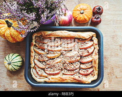 Top view on cooked open apple pie with nuts and cinnamon. Thanksgiving treat concept. Gifts of Autumn Heather, Pumpkins, Apple Pie - Stock Photo