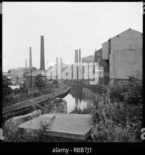 Weavers' Triangle, Burnley, Lancashire, 1966-1974. A view looking south-east along the Leeds and Liverpool Canal from Westgate Bridge showing mills an - Stock Photo