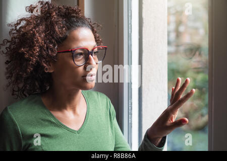Sad african american girl looking out of the window
