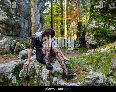 Beautiful young female in nature is sitting atop big rock in bad mood negative feeling concerned looking down hiding face feeling miserable - Stock Photo