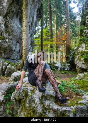 Beautiful young female in nature is sitting atop big rock in bad mood negative feeling concerned looking down hiding face - Stock Photo