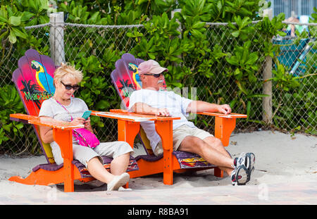 MIAMI, FLORIDA - JANUARY 21, 2018: Elderly couple sitting in beach chairs. With selective focus - Stock Photo