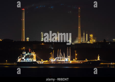 Tanker discharging at night at the Valero Oil Refinery Pembroke West Wales Great Britain - Stock Photo