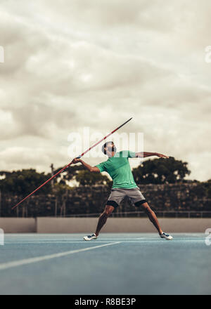 Man in position to throw a javelin in a track and field stadium. Athlete doing javelin training in the field on a cloudy day. - Stock Photo