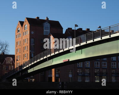 Bremen, Germany - Steel bridge across the river Weser leading to the Teerhof peninsula with red brick buildings in the background under a clear blue s - Stock Photo