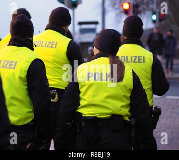 Bremen, Germany - Group of police officers in black uniforms and hi-viz vests patrolling the christmas market - Stock Photo