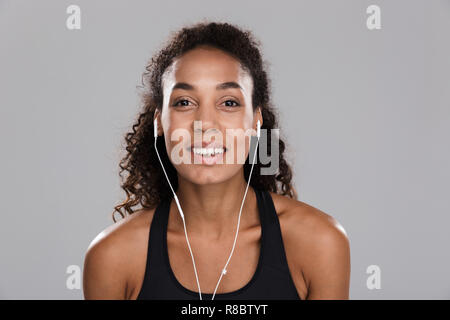 Portrait of an afro american young cheerful sportswoman isolated over gray background, listening to music with earphones - Stock Photo