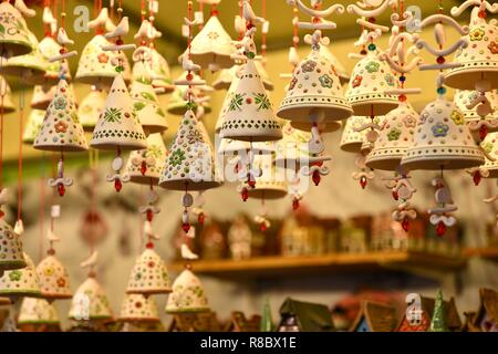 Florence, ITALY - DECEMBER 2018: small decorated bells hanging from the roof at the Christmas market in front of the 'Basilica of Santa Croce'. Christ - Stock Photo