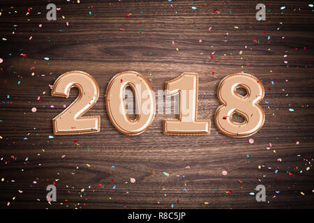 Balloons forming 2018 with confetti on wooden surface - Stock Photo