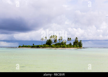 A small islet (motu) overgrown with palm forest somewhere in the lagoon of South Tarawa atoll in bad cloudy weather, Kiribati, Gilbert islands, Micron - Stock Photo