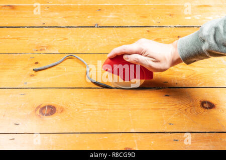 How to Fill Gaps in Floorboards and Seal Floorboards to Prevent Draughts and Heat Loss. Best way to draught-proof stripped wooden floors. Using the Applicator - Stock Photo