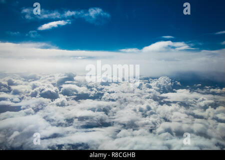 Aerial view White clouds in blue sky. Top view. View from the plane. Aerial bird's eye view. Aerial top view cloudscape. Texture of clouds. View from  - Stock Photo