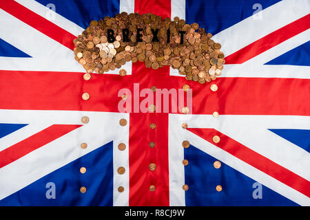 Brexit concept Union Jack and EU flag separated.Piggy coin bank on side,1p and 2p coins. - Stock Photo